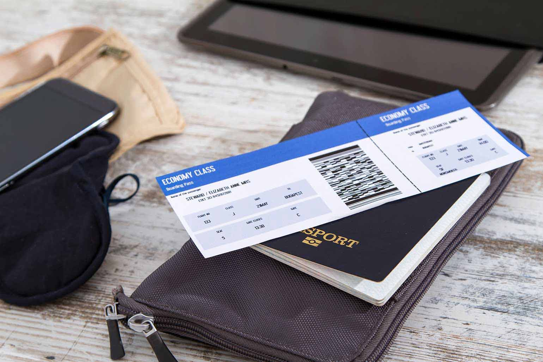 Billet d'avion, passeport et appareils électroniques prêts pour le voyage.