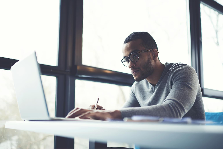 Professionnel afro-américain spécialiste des TI, travaillant à la pige dans un café sur un ordinateur portable à l'aide d'Internet sans fil, à des projets visant la mise à jour de logiciels et l'amélioration du code d'applications.