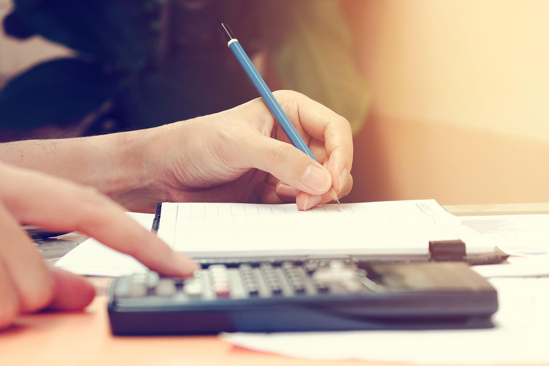 Plan rapproché d'une jeune femme qui fait des calculs chez elle, à l'aide d'une calculatrice, tout en prenant des notes à la main dans un cahier. Concept d'épargne et de finances.