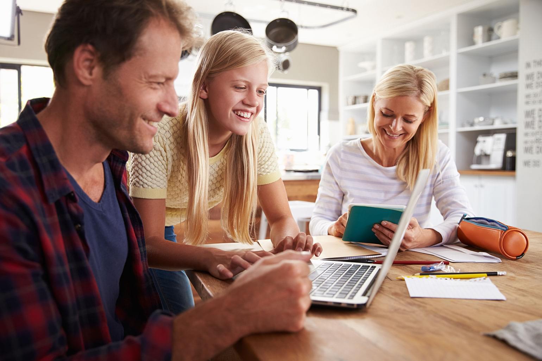 Jeune fille qui aide ses parents à apprivoiser une nouvelle technologie.