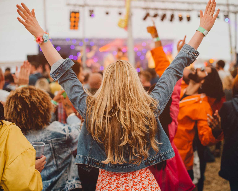 Une jeune femme regardant la scène, debout au milieu de la foule, pendant un festival de musique.