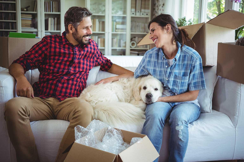 Un couple est assis sur un sofa avec un chien dans sa nouvelle maison.