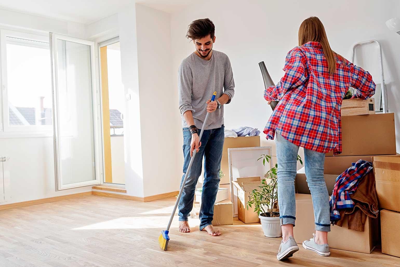 Un jeune couple déballe ses cartons et fait le ménage après son déménagement.