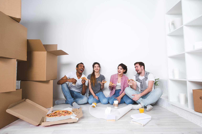 Nouveau logement. Des amis (qui mangent de la pizza) se retrouvent dans leur nouvel appartement, après avoir déballé leurs cartons.