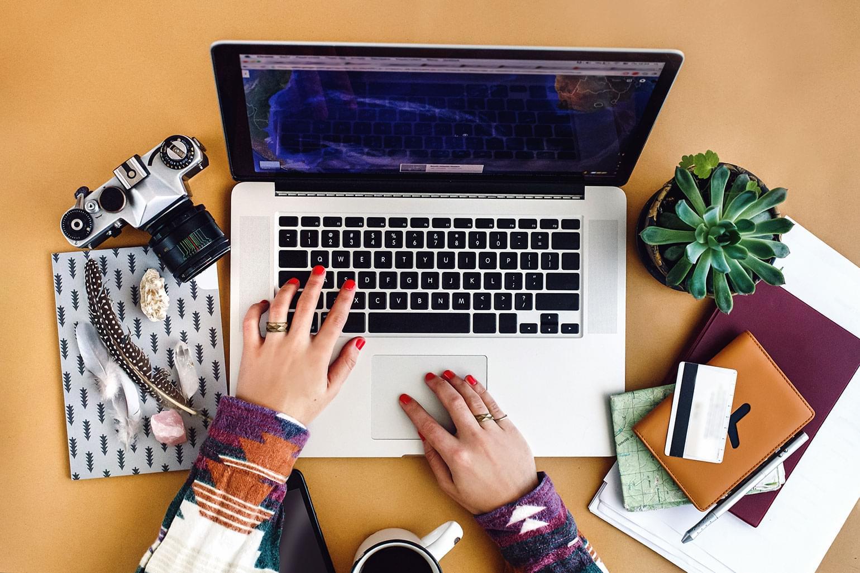 « Jeune femme planifiant ses vacances sur un ordinateur portable, vue d'en haut.