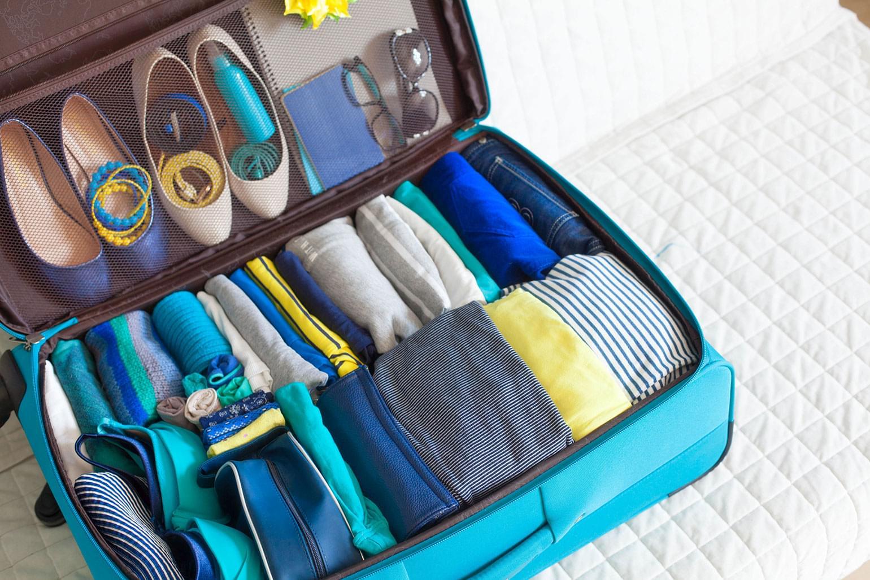Intérieur d'une valise impeccable : vêtements roulés et organisés.