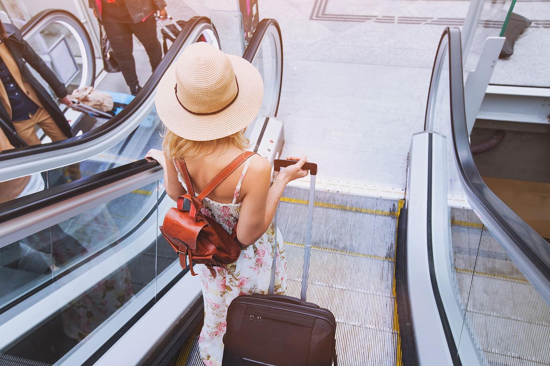 Voyageuse élégante tenant sa valise sur l'escalier roulant d'un aéroport.
