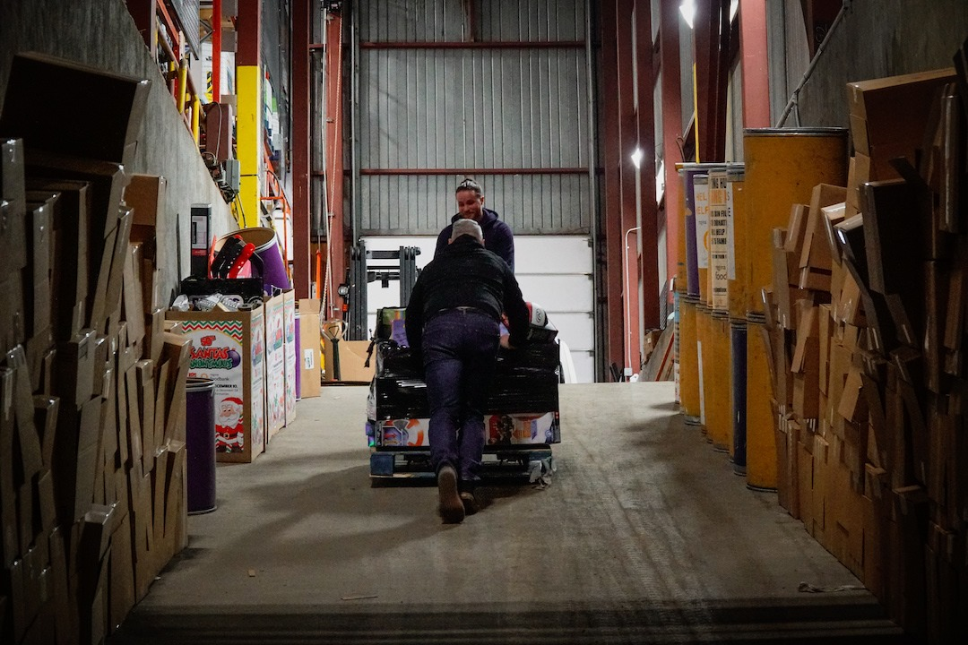 Two volunteers push a trolly loaded with food up a ramp inside the Regina Food Bank