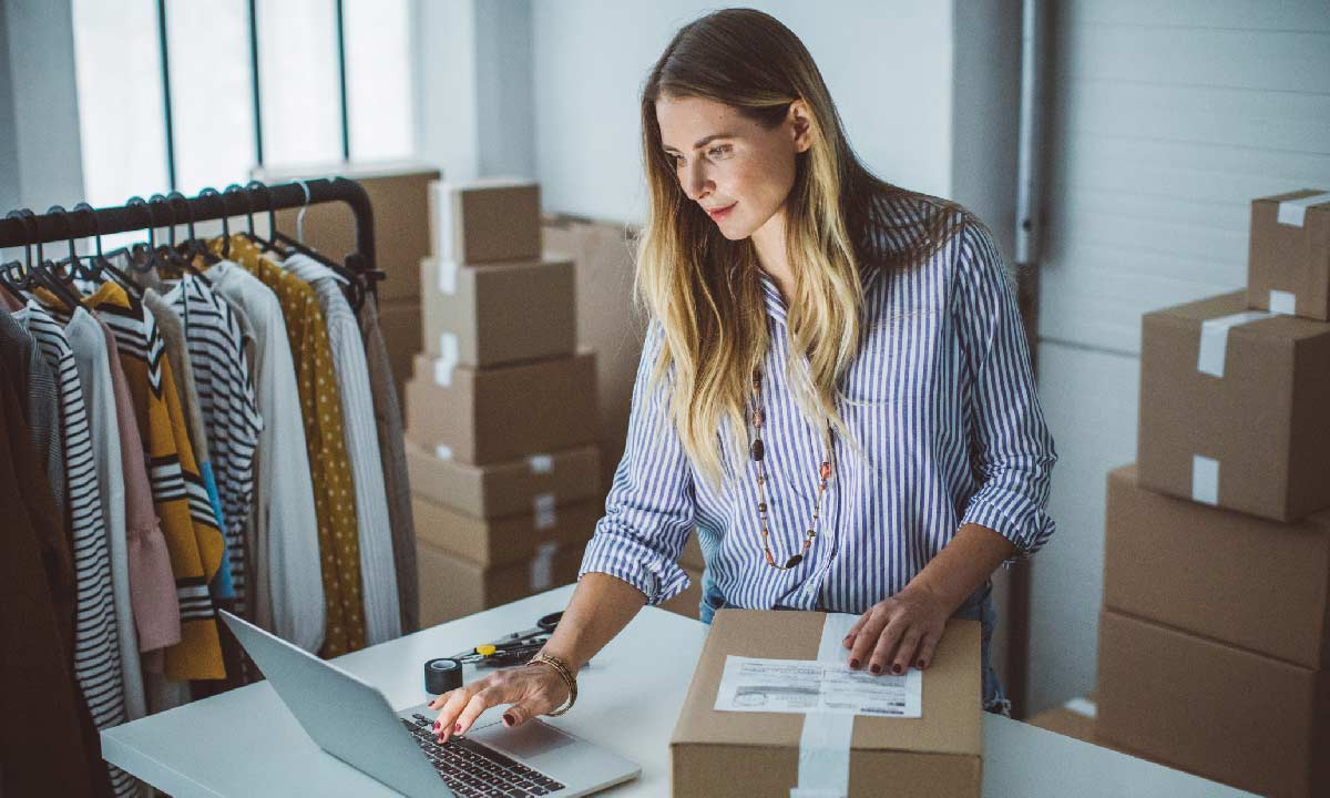 Women, owener of small business packing product in boxes, preparing it for delivery.