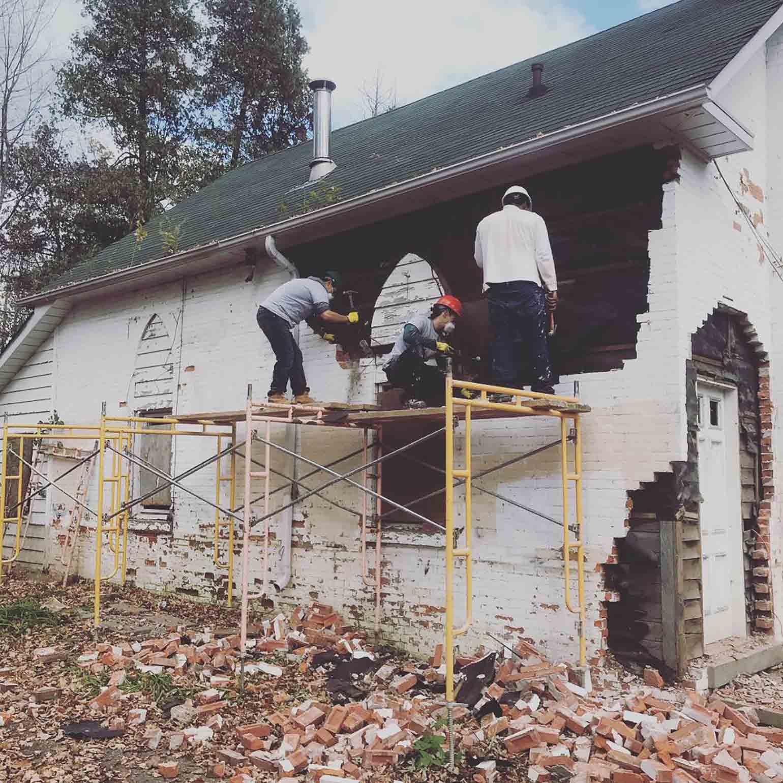 Un constructeur et un apprenti transportent du bois sur un chantier de rénovation. Trois travailleurs aident à démolir un mur de briques blanches pour rénover une maison destinée à loger des sans-abri.