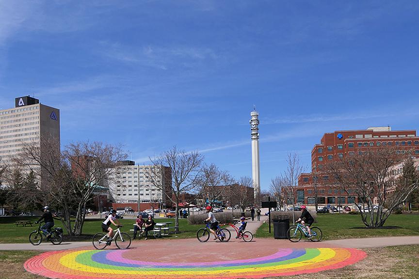 Une place de parc par une journée ensoleillée au centre-ville de Moncton avec des jeunes à vélo et un arc-en-ciel peint sur le trottoir.