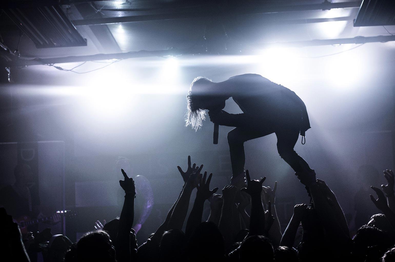 Foule acclamant un chanteur à un concert dans un bar.
