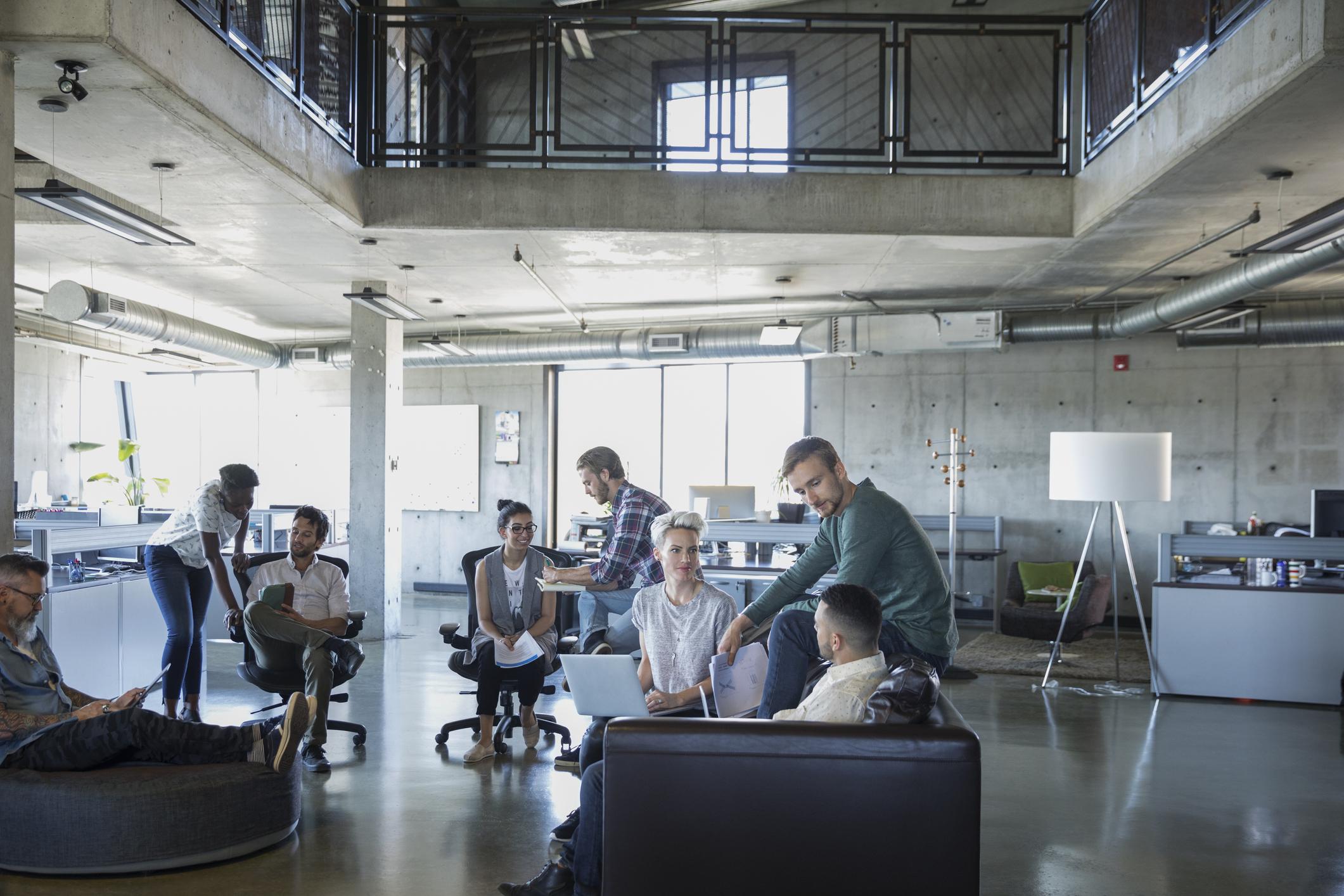 Des gens d'affaires discutent dans un bureau à aire ouverte