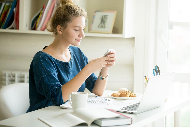 Portrait d'une belle jeune femme décontractée tenant un téléphone intelligent. Assise derrière un bureau moderne, à la maison ou dans une résidence étudiante, et entourée d'un ordinateur portable, de livres, d'un café et de biscuits, elle regarde l'écran et utilise une application ou un service de messagerie texte.